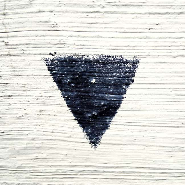 Black triangle on white wall